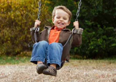 child on a swing in a play park